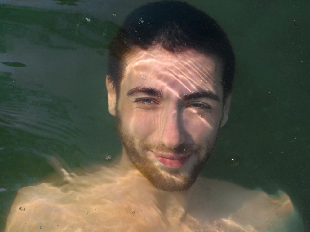 Junger Mann blickt von unter dem Wasserspiegel empor